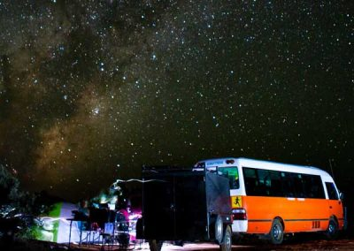 Smaller photo of the Why Not Bus stopped at night on one of theire Perth to Broome adventures. You can also see Backpackers near a fire.