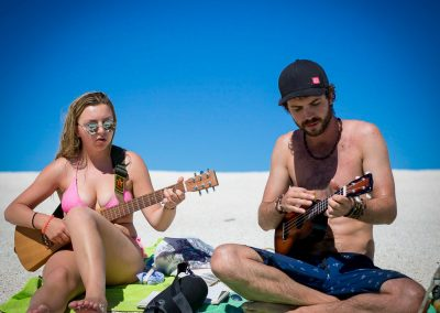 Two backpackers playing guitar on an exmouth beach after their whale shark tour.