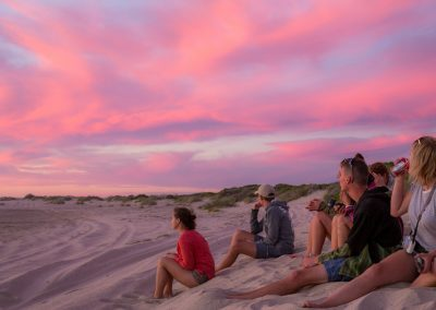 6 Backpackers from the Why Not Bus sitting on beach as part of their Perth to Broome tour.