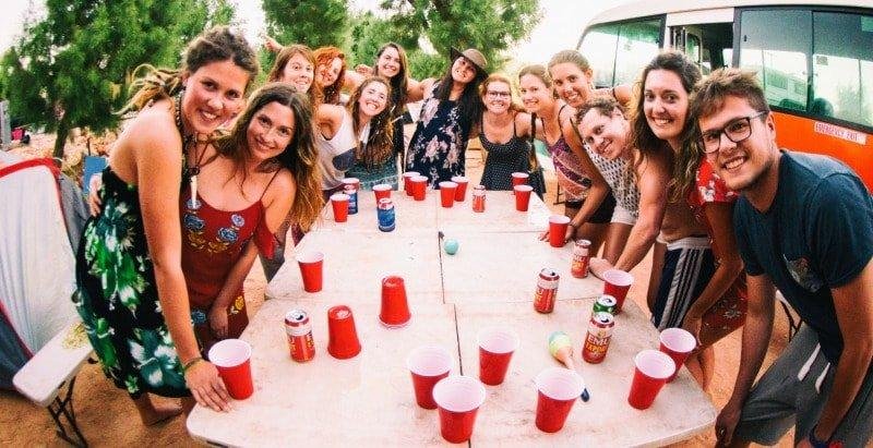 playing beer pong on the western australia backpacker tours. Why Not Bus in the background